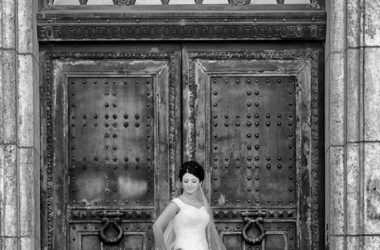 Der Hochzeitsfotograf in Hannover, Michael Siebert, setzt Braut allein vor Kirchentuer, schwarz weiß in Szene.