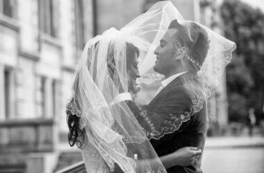 Der Hochzeitsfotograf in Hannover, Michael Siebert, setzt Brautpaar unter Schleier, schwarz weiß in Szene.